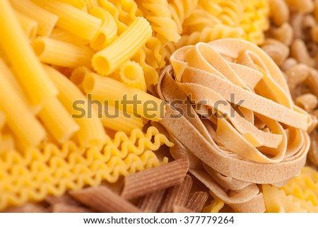 Assortment of italian pasta, five different varieties separated with curly spaghetti and bunch of noodles in the middle. Raw pasta texture background. - stock photo