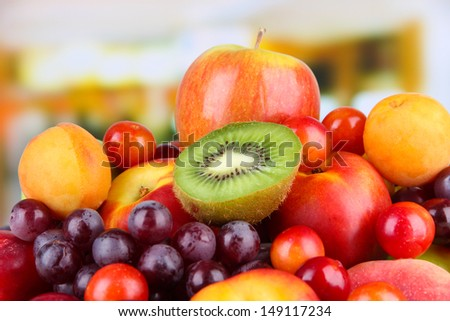 Assortment of juicy fruits on bright background - stock photo