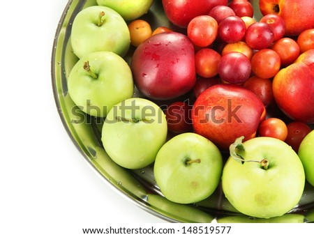 Assortment of juicy fruits on plate, isolated on white