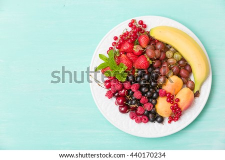 Assortment of juicy fruits on white plate and turquoise table background. Banana, strawberries, blueberries, raspberries, gooseberry, blackcurrant decorated with mint for summer dessert or snack. - stock photo