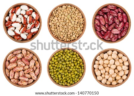 Assortment of legumes in wooden bowls isolated on white - stock photo