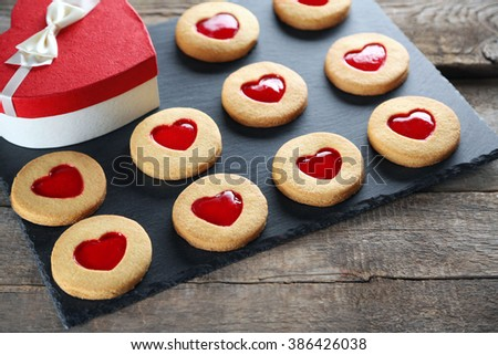 Assortment of love cookies with gift box on grey stand - stock photo
