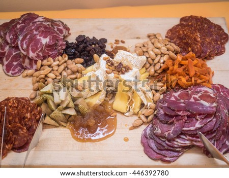 Assortment of meats and cheeses served on wooden board