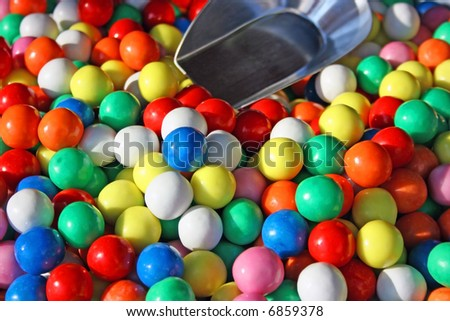 Assortment of multicolored round bonbons in a barrel accompanied with a scoop to be picked out on a market.