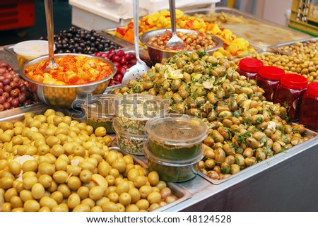assortment of olives, pickles and salads on market stand - stock photo
