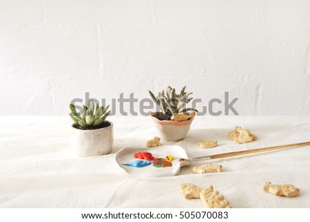 assortment of plants, biscuits and painting tools against a white brick interior