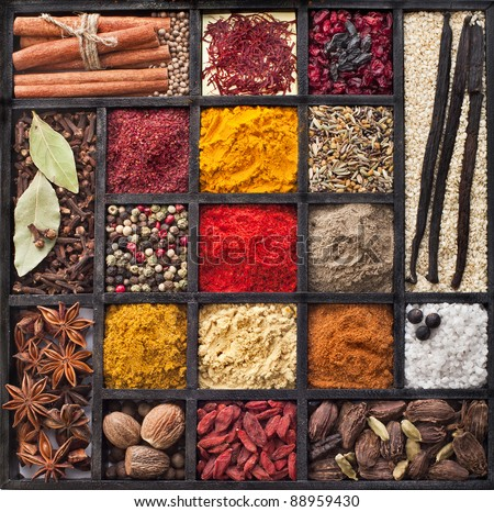 Assortment of powder spices on spoons in wooden box background