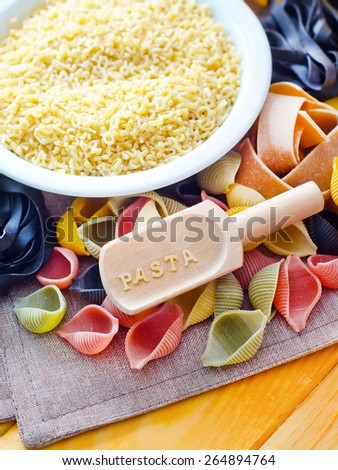 assortment of raw pasta and wheat on wooden background - stock photo