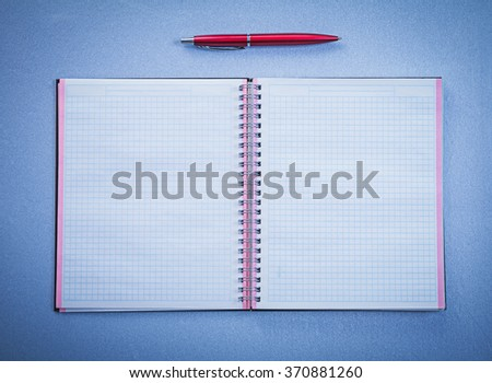 Assortment of red ball-point pen open copybook office concept. - stock photo