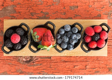 Assortment of ripe fresh autumn berries displayed on a wooden board in individual dishes with raspberries, blackberries, blueberries and raspberries on a grungy wooden table with peeling paint - stock photo