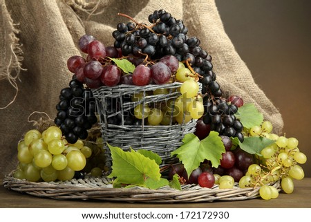 assortment of ripe sweet grapes in basket, on brown background - stock photo