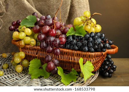 assortment of ripe sweet grapes in basket, on burlap background - stock photo