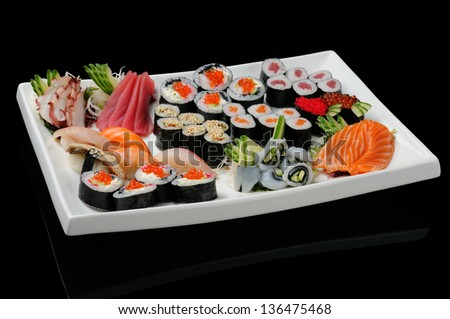 Assortment of rolls, sushi and sashimi served on white plate - stock photo