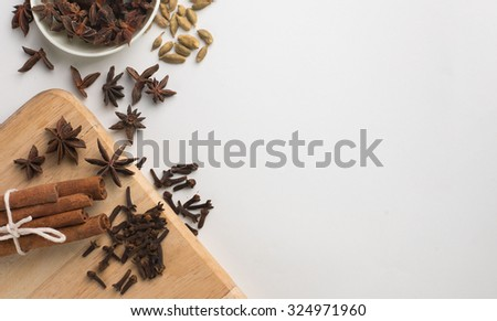 Assortment of spice,cinnamon,star anise,cardamom,coriander seed and clove with cutting board over white background - stock photo