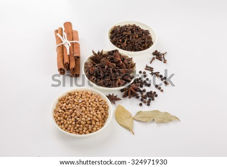 Assortment of spice,Star anise,coriander seed,clove in white bowls and pepper corn,bay leave,cinnamon over white background - stock photo