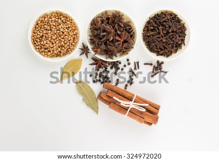 Assortment of spice Star anise,coriander seed,clove in white bowls and pepper corn,bay leave,cinnamon over white background - stock photo