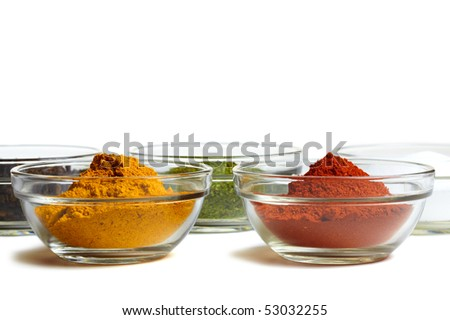 Assortment of spices ( curry, pepper, salt, herbs, chili ) on white background