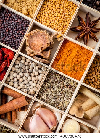Assortment of spices food cooking ingredients in wooden box set up on wooden table. - stock photo