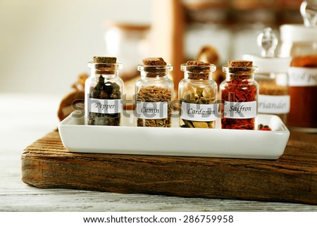 Assortment of spices in glass bottles on cutting board, on wooden background - stock photo
