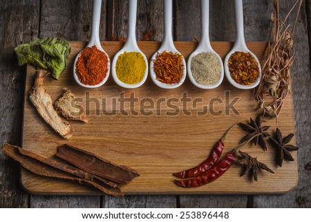 Assortment of spices in the spoons for prepare tasty food with soft shadow in the wooden background and a paper for your text - stock photo