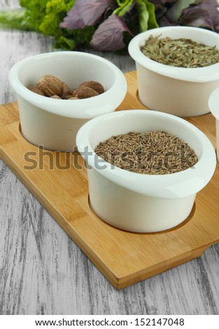 Assortment of spices in  white  bowls, on wooden background