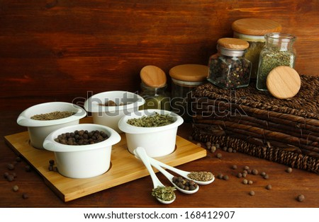 Assortment of spices in  white spoons and bowls, on wooden background