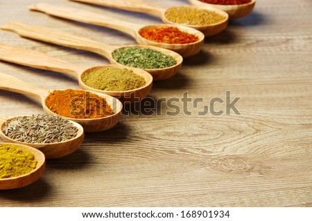 Assortment of spices in wooden spoons on wooden background - stock photo