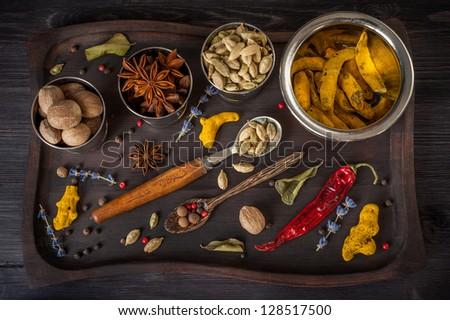 Assortment of spices: star anise, turmeric, nutmeg, cardamom, lavender, allspice and lemon grass in a vintage tray. - stock photo