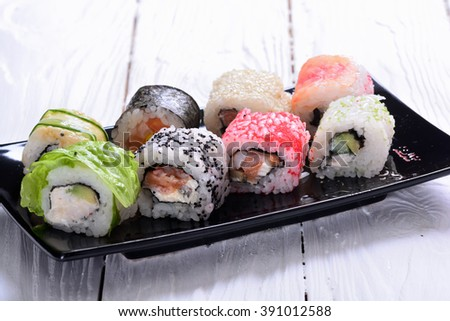 Assortment of Sushi rolls on wooden background - stock photo