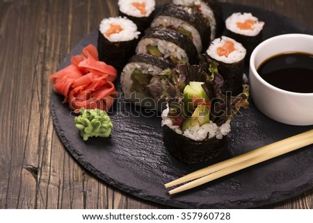 Assortment of sushi rolls with salmon and vegetables, served with soy sauce and chopsticks. Selective foucs - stock photo