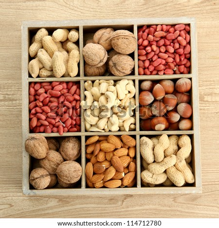 assortment of tasty nuts in  wooden box on table - stock photo