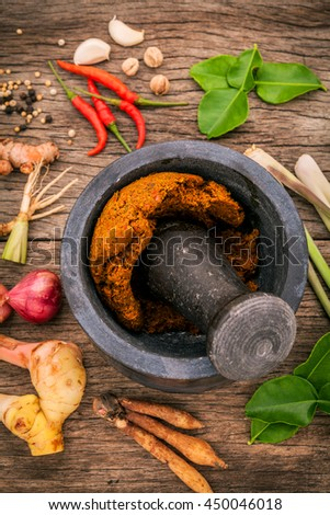 Assortment of Thai food Cooking ingredients and spice red curry paste ingredient of thai popular food on wooden background. Spices ingredients chilli ,pepper, garlic,galanga and Kaffir lime leaves .