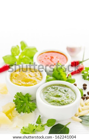 Assortment of three colorful hot sauces with ingredients - stock photo
