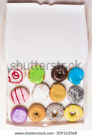 assortment of various colorful donuts in a white paper box , top view - stock photo