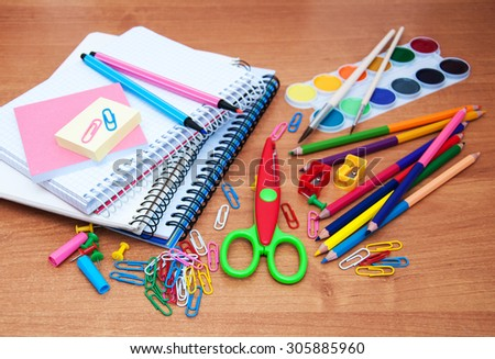 assortment of various school items on a wooden background