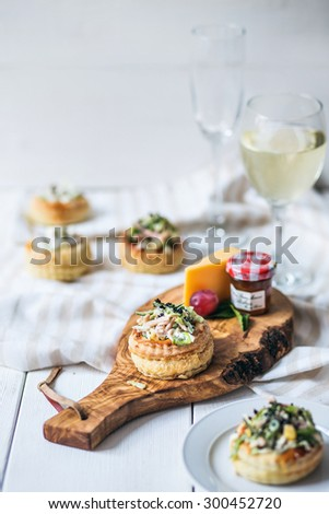 Assortment of various types of appetizers and glass of wine on wooden cutting board