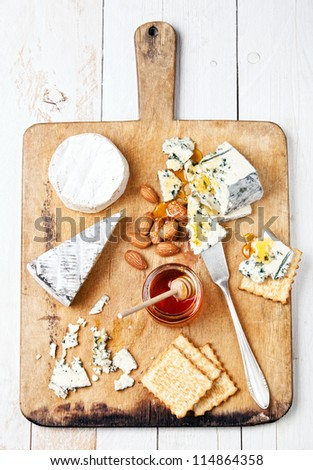 Assortment of various types of cheese on wooden board - stock photo