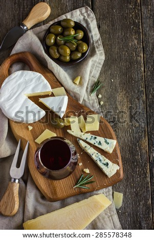 Assortment of various types of cheese on wooden board, top view - stock photo