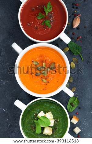 assortment of vegetable cream soup on a dark background, top view - stock photo