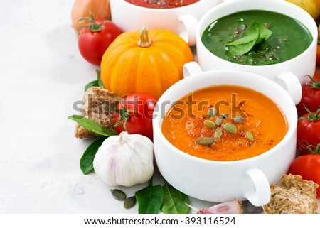 assortment of vegetable cream soups and ingredients on white background, closeup, horizontal - stock photo