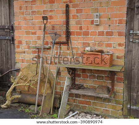 Assortment of Vintage Garden Tools Leaning against a Brick Wall of Stables on a Farm near the Rural Village of Tissington within the Peak District National Park, Derbyshire, England, UK - stock photo