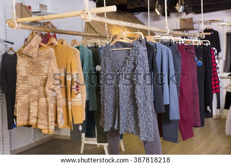 Assortment of warm clothing and accessories in modern garment store - stock photo