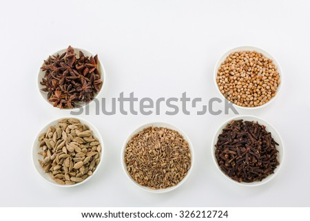 Assortment spice,clove and star anise,cardamom,cumin seed and coriander seed in white bowl over white background  - stock photo
