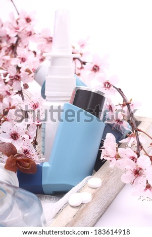 Asthma inhalers with blossoming tree branches on wooden tray over white - stock photo