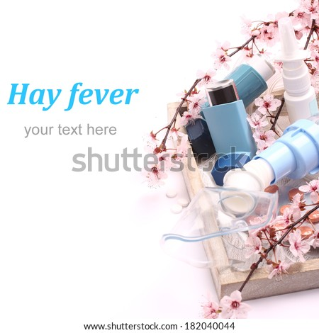 Asthma inhalers with inhalation mask and blossoming tree branches on wooden tray over white, with easy removable sample text - stock photo