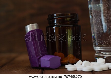 Asthma inhalers with medicines on a beautiful brown background. Bottle pills.Concept of asthma.