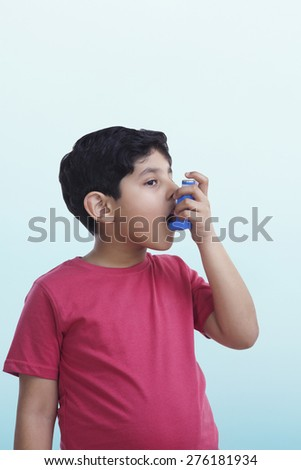 Asthmatic boy using an inhaler - stock photo