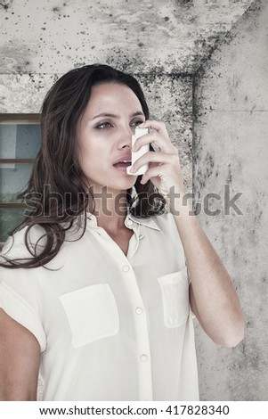 Asthmatic brunette using her inhaler against image of a room corner - stock photo