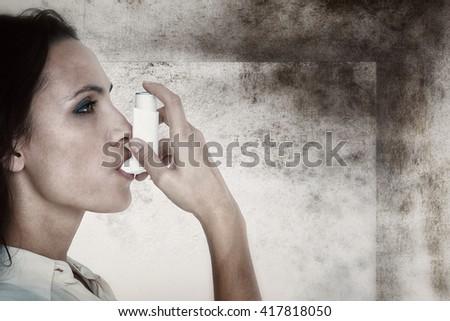 Asthmatic brunette using her inhaler against image of room corner - stock photo