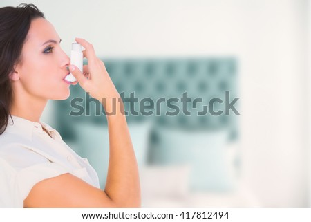 Asthmatic brunette using her inhaler against pillow in a bed - stock photo
